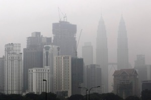 epa04931033 Malaysia's Petronas Towers (R) building and shrouded by haze in Kuala Lumpur, Malaysia, 15 September 2015. Schools were closed in the Malaysian capital and outlying areas amid worsening haze caused by forest and plantation fires in neighbouring Indonesia, officials said.  EPA/AHMAD YUSNI